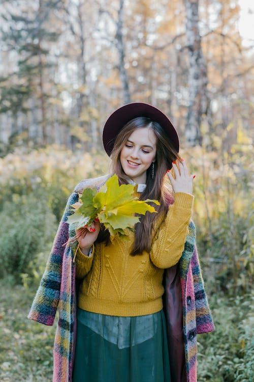 노란색 꽃 꽃다발을 들고 노란색 긴 소매 셔츠에 여자