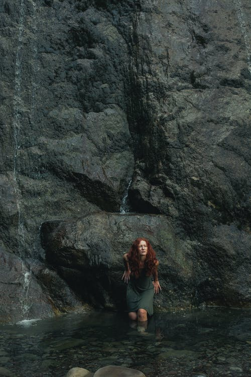 Redhead woman standing in lake near waterfall