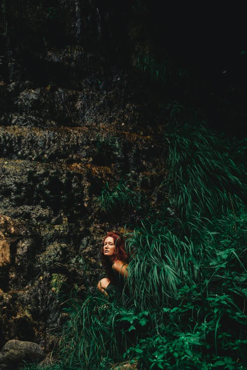 Woman sitting in lush bush