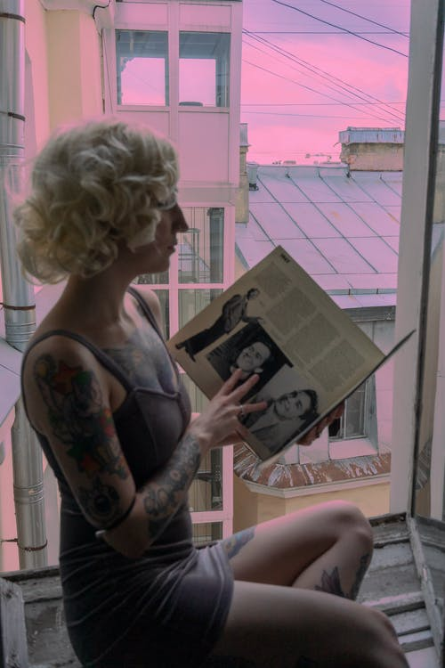 Side view of unrecognizable female with blond hair and tattoos sitting on windowsill with tucked leg near opened window while reading book against pink sky
