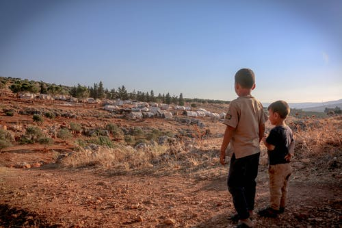 Back view full body of ethnic homeless kids standing on dry ground with tents at distance
