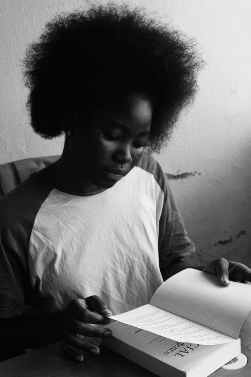 Black and white of young concentrated African female with Afro hairstyle reading textbook at table