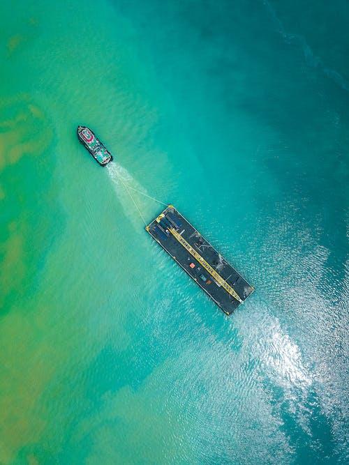 Aerial view of boat pulling big shipment platform on seawater