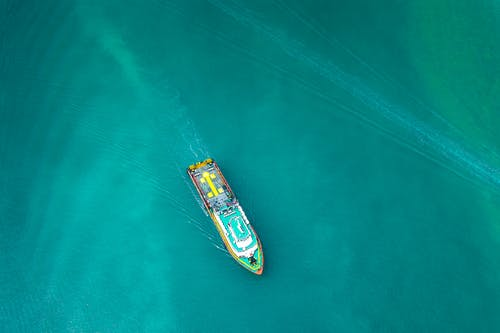 Aerial view of contemporary industrial boat floating along turquoise rippling ocean on clear day