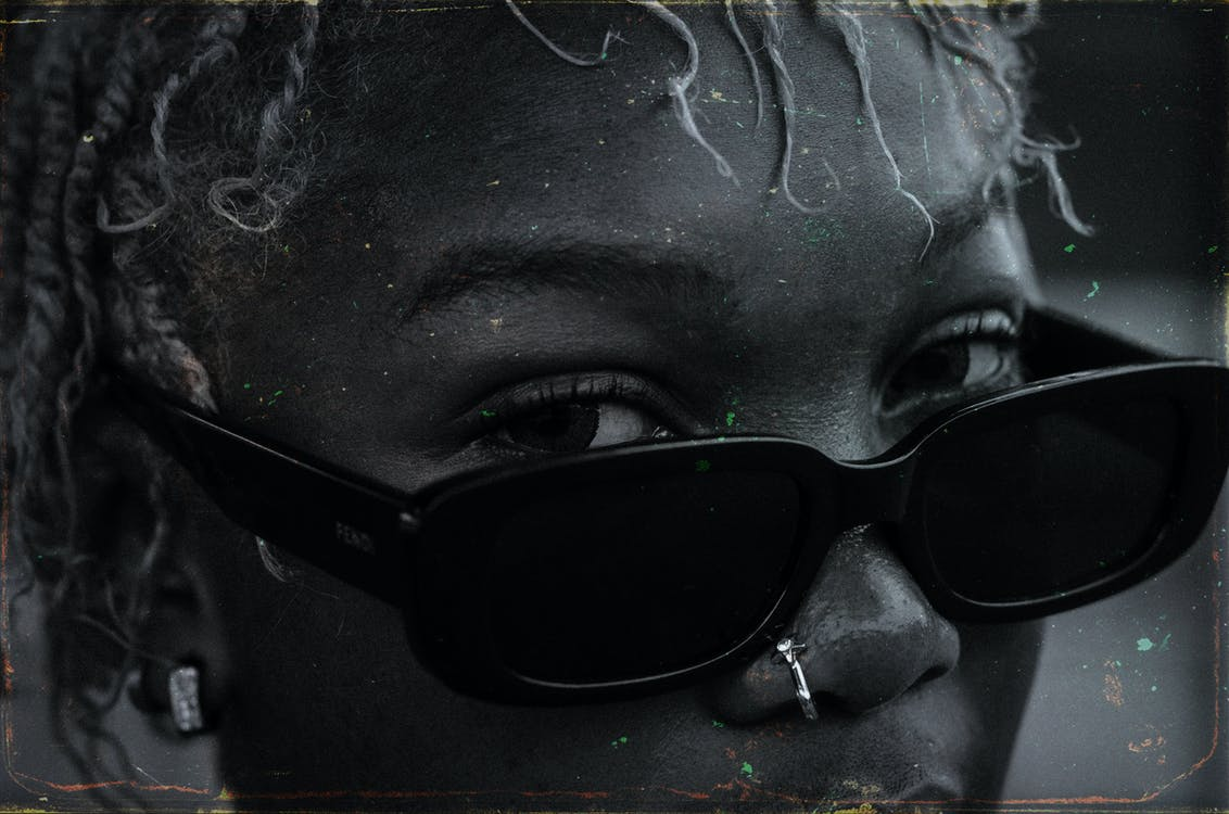 Black and white crop attractive African American female with African hairstyle and nose piercing wearing trendy sunglasses on blurred street and looking at camera attentively