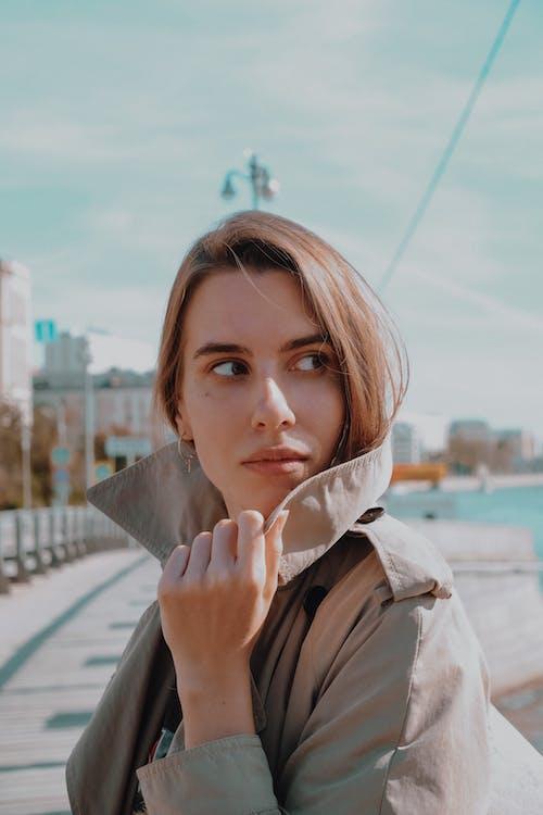 Woman in Brown Coat Leaning on Railings