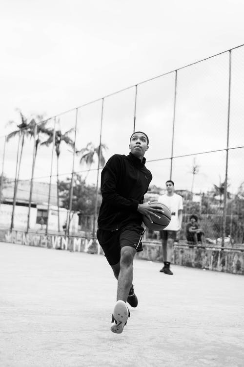 Concentrated young black athlete running with ball during basketball training
