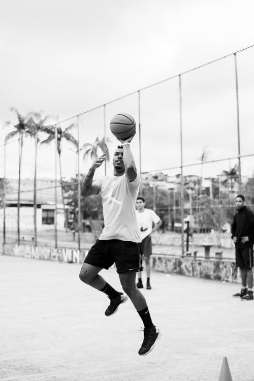 Man in White T-shirt and Black Shorts Playing Basketball in Grayscale Photography
