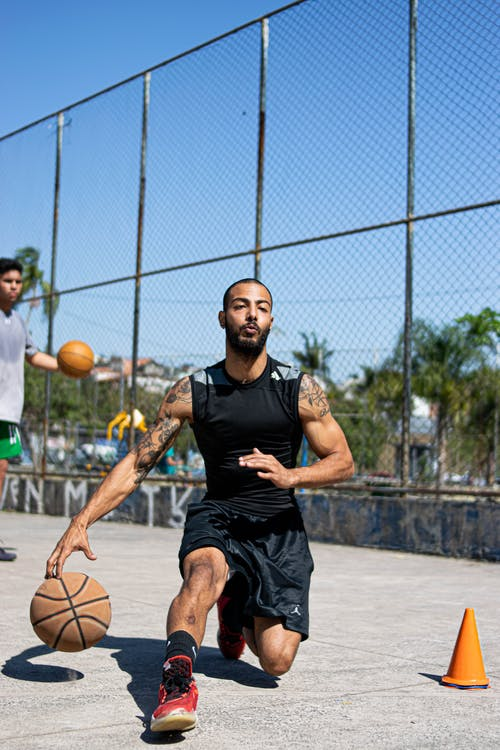Man in Black Nike Tank Top and Black Shorts Playing Basketball