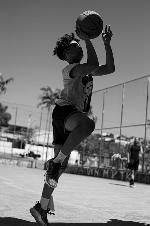 Grayscale Photo of Woman in Tank Top and Shorts