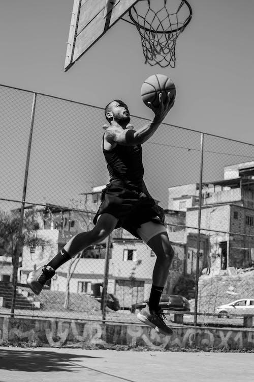 Grayscale Photo of Man Playing Basketball