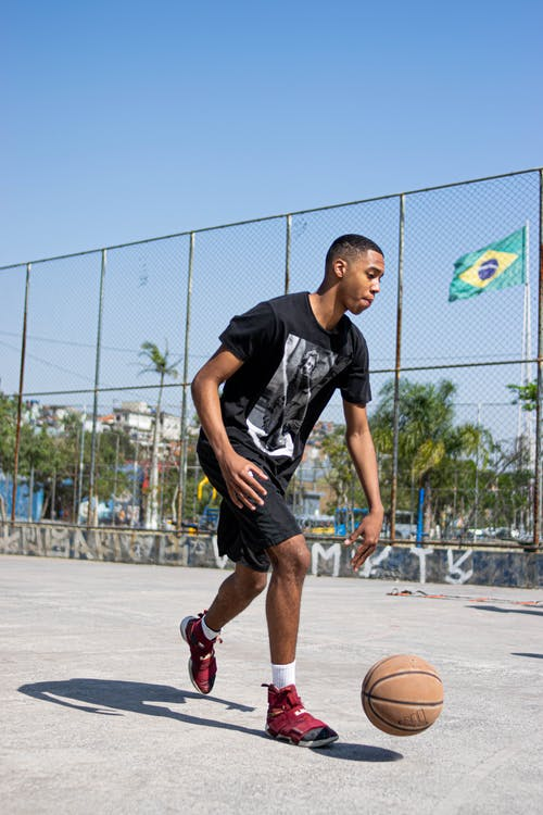 Man in Black Crew Neck T-shirt and Black Shorts Playing Basketball