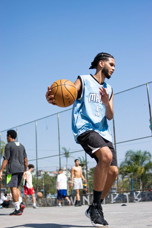 Man in Blue and White Basketball Jersey Playing Basketball