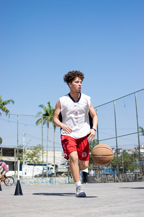 Man in White Nike Crew Neck T-shirt and Red Shorts Playing Basketball