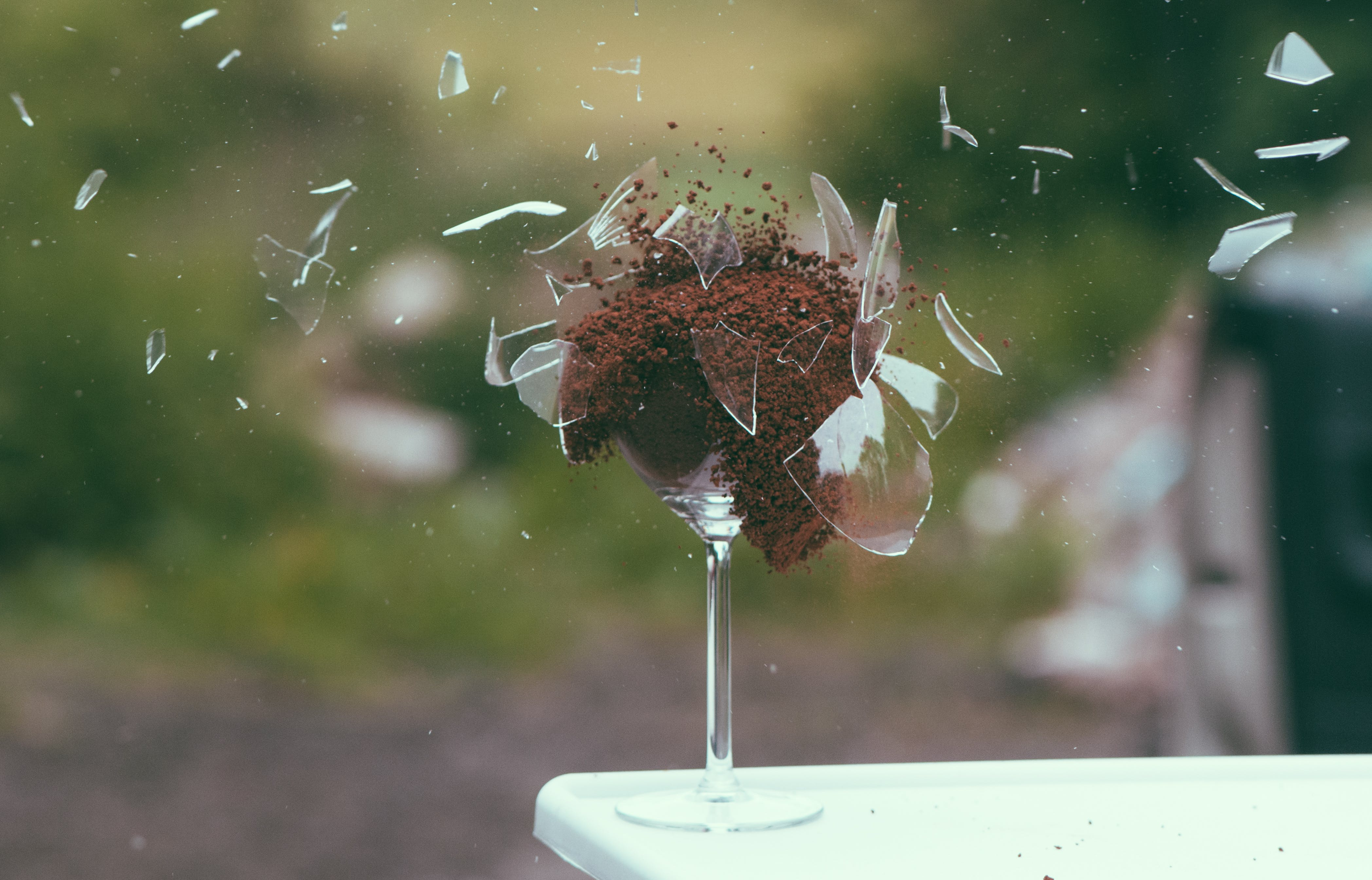 Selective Focus Photography of Broken Wine Glass With Brown Powder