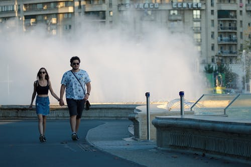 2 Women Standing on Gray Concrete Bridge Near Water Fountain