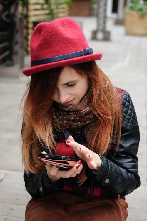 Stylish woman using smartphone on street