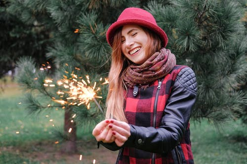 Delighted woman with burning Bengal lights in park