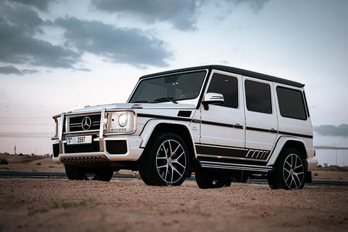 White and Black Jeep Wrangler on Brown Dirt Ground Under White Clouds