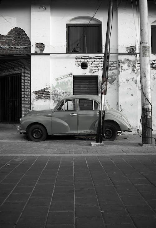 Parked retro car near shabby building