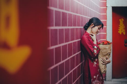 Side view of young charming ethnic lady in traditional outfit standing near wall with closed eyes and flower bouquet