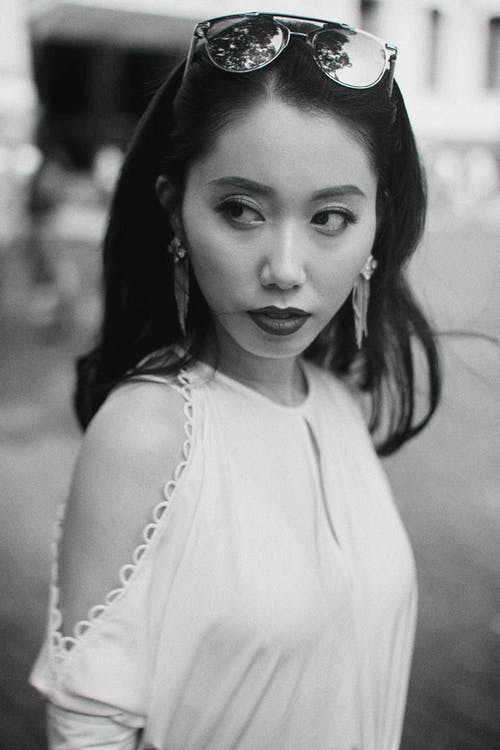 Trendy Asian woman standing on blurred street