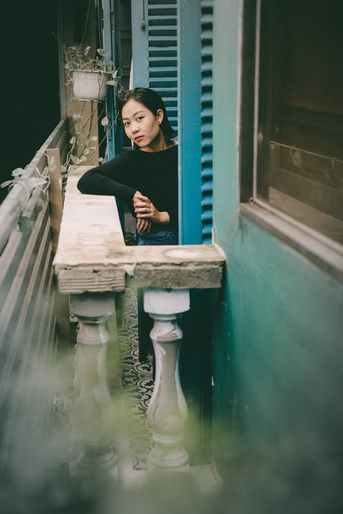 Positive Asian woman leaning on balcony railing