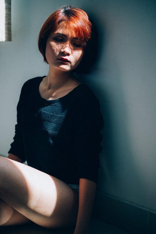 Unhappy female sitting on floor at sunlight