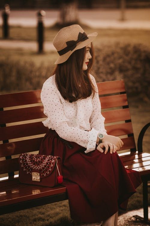 Stylish woman in elegant outfit sitting on bench