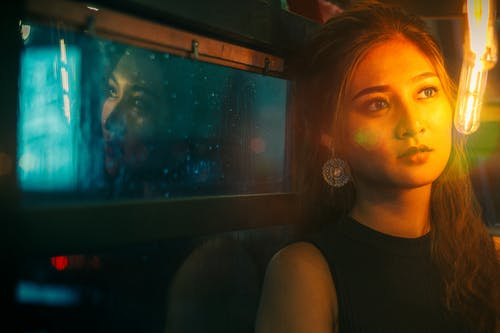 Young calm woman sitting near illuminated lamp