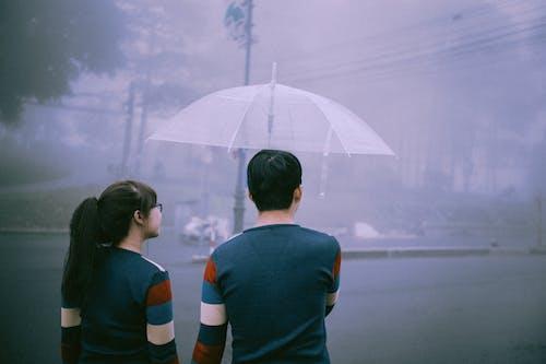 2 Men in Blue and Orange Shirt Holding Umbrella
