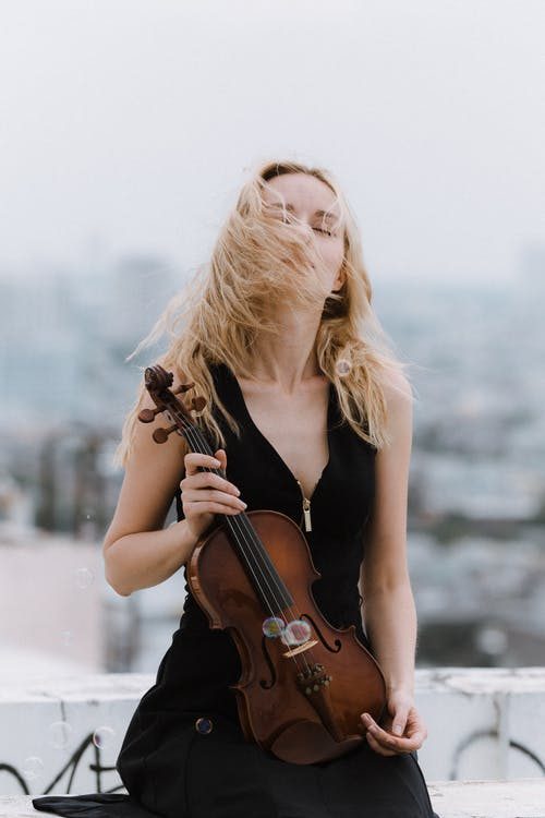 Woman with violin standing on roof