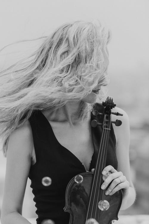 Black and white female musician holding music instrument while blowing hair on wind