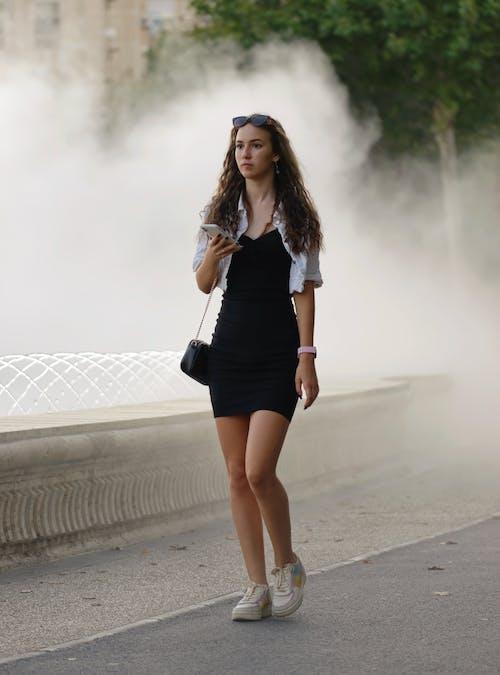 Woman in Black Mini Dress Standing on Gray Concrete Road