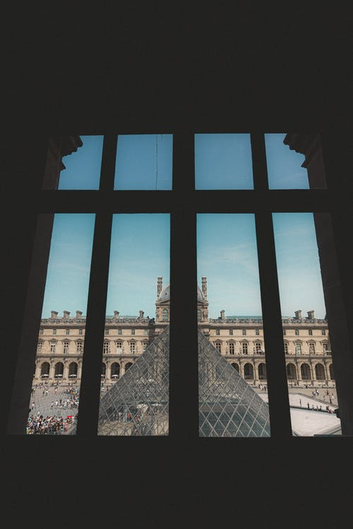 Through window view of historic Louvre Museum square with famous glass pyramid and heritage architecture
