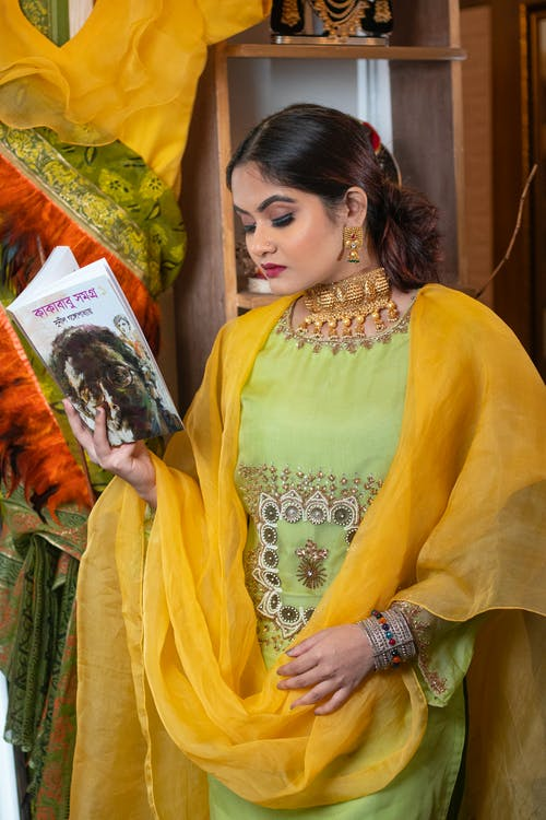 Woman in Yellow and Green Floral Sari Holding White Book