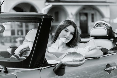 Attractive woman sitting in luxurious cabriolet