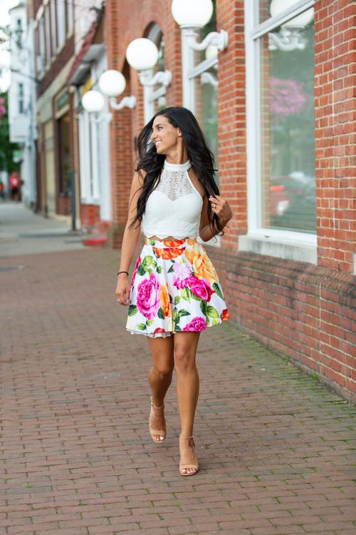 Full body of positive young female in trendy blouse and skirt promenading on street while looking away in summer weather