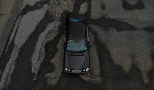 High Angle Shot of a Car on Gray Asphalt Road