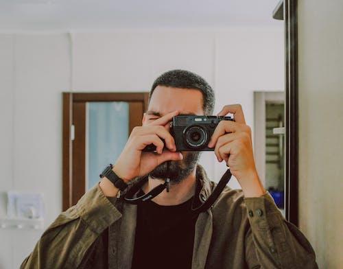 Bearded man taking selfie near mirror
