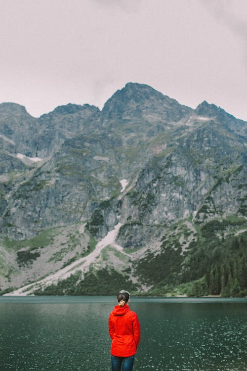Back View of a Person in Red Jacket Viewing the Mountain Lake Scenery
