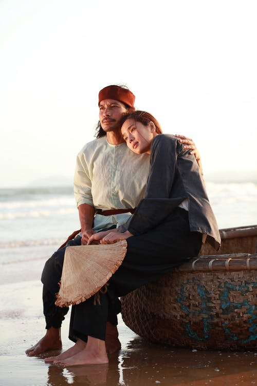 Young Asian man in traditional apparel embracing pondering barefoot beloved while sitting on boat on ocean coast and looking away