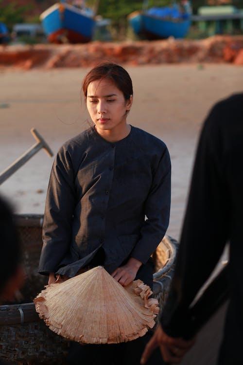 Melancholic ethnic woman in boat on sea