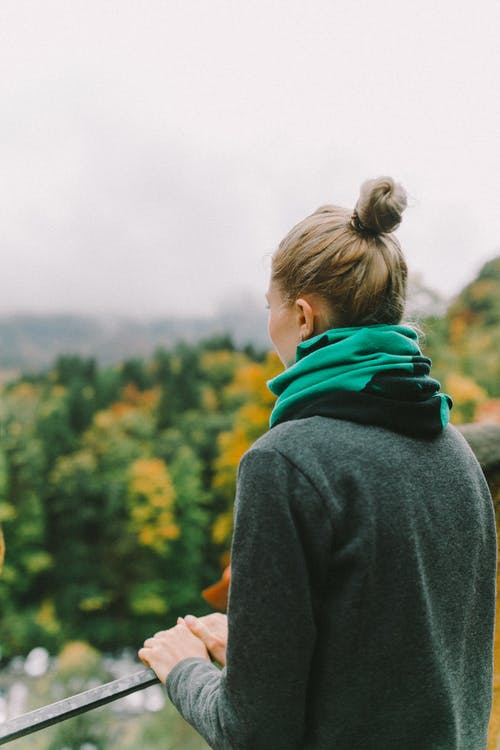 Woman in Gray Hoodie Standing Near Green Trees