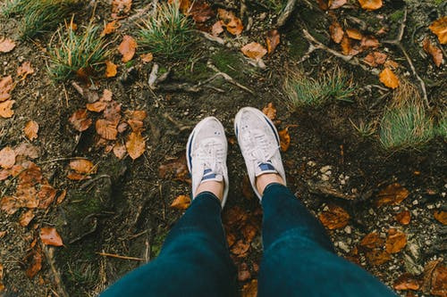 Person in Blue Denim Jeans and White Sneakers Standing on Dried Leaves