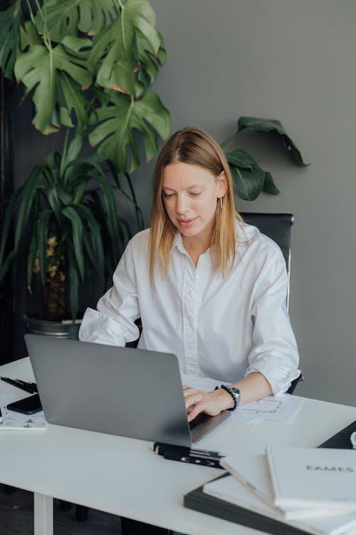 Woman in White Dress Shirt Using Macbook