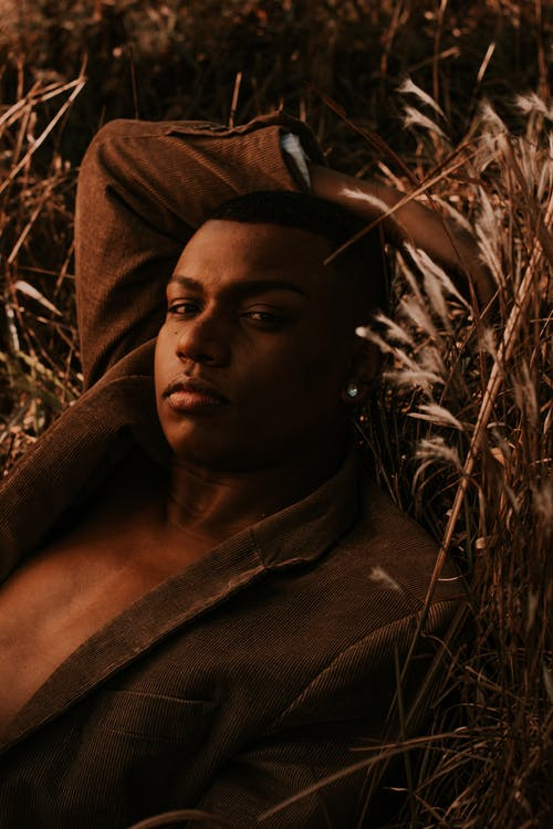 Dreamy African American male in brown jacket looking at camera while chilling on dry grass with hand behind head