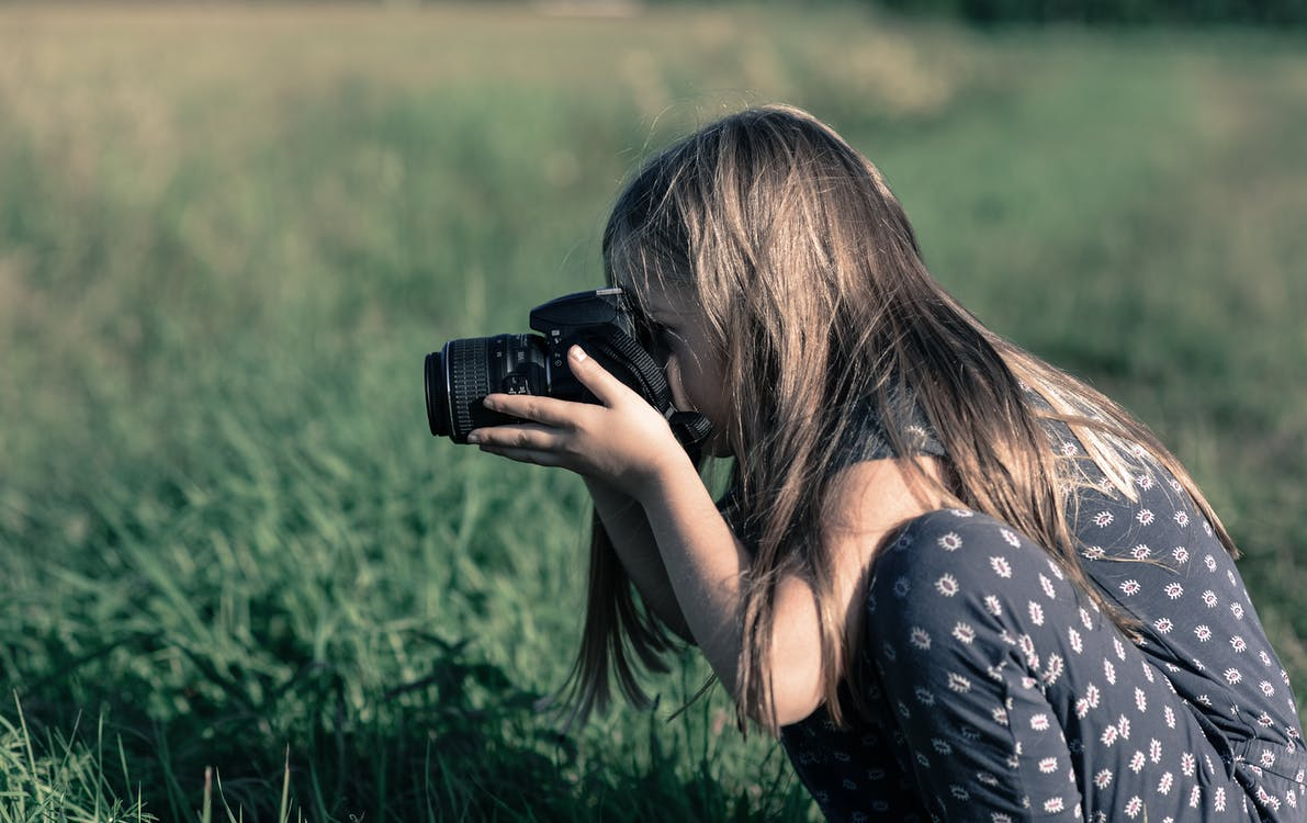 Girl Holding Dslr Camera on Green Grass Field