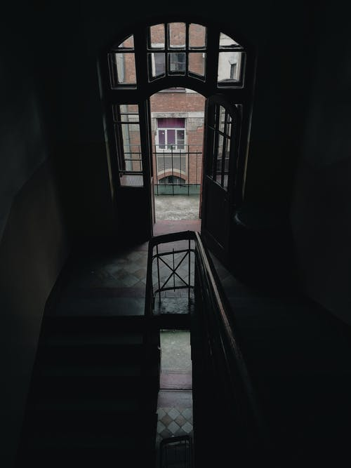 From above of staircase with railings inside multistory residential house with window and metal fence located near building on street