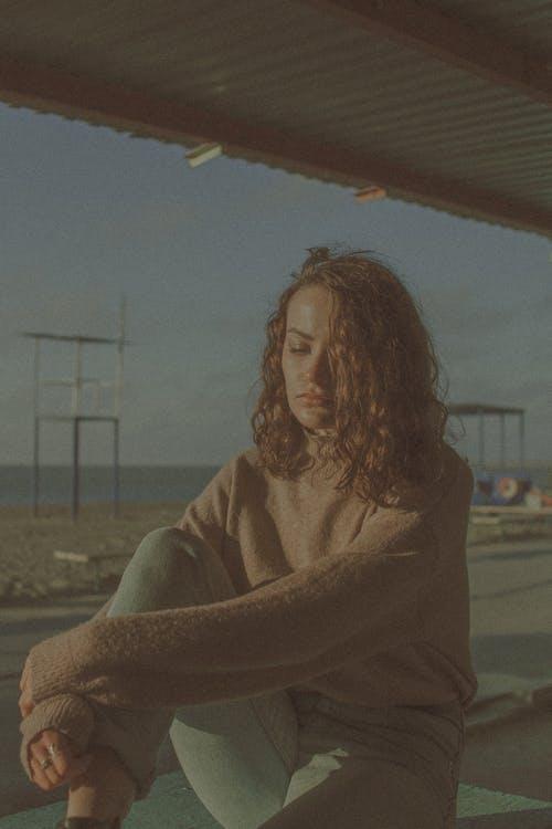 Pensive woman sitting on seashore and hugging knee